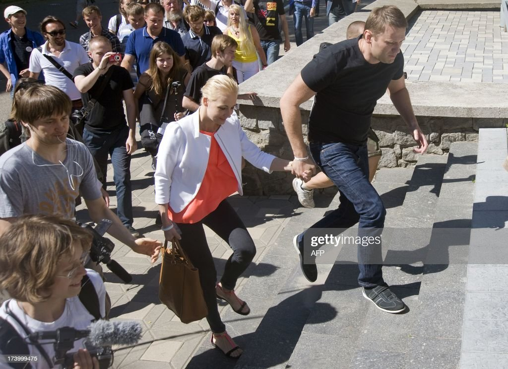 Russia's top opposition leader Alexei Navalny and his wife Yulia hold hands after leaving the courtroom in Kirov on July 19, 2013. A Russian court on Friday unexpectedly freed protest leader Alexei Navalny pending his appeal against a five-year sentence on embezzlement charges, after his jailing prompted thousands to take to the streets in protest. The judge in the northern city of Kirov ruled that keeping President Vladimir Putin's top opponent in custody would deprive him of his right to stand in mayoral elections in Moscow on September 8.