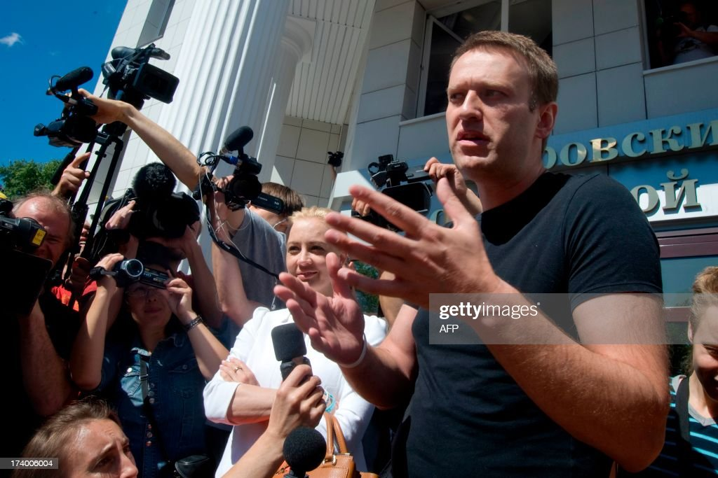 Russia's top opposition leader Alexei Navalny (R) and his wife Yulia speak after leaving the courtroom in Kirov on July 19, 2013. A Russian court on Friday unexpectedly freed protest leader Alexei Navalny pending his appeal against a five-year sentence on embezzlement charges, after his jailing prompted thousands to take to the streets in protest. The judge in the northern city of Kirov ruled that keeping President Vladimir Putin's top opponent in custody would deprive him of his right to stand in mayoral elections in Moscow on September 8. AFP PHOTO/SERGEI BROVKO