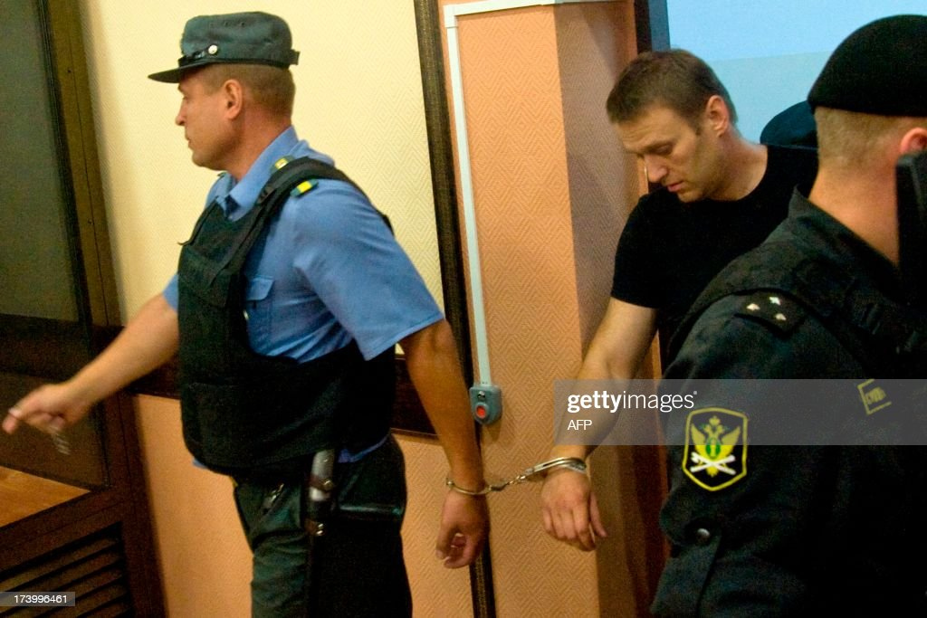 Russia's top opposition leader Alexei Navalny (R) arrives in the courtroom in Kirov on July 19, 2013. A Russian court on Friday unexpectedly freed protest leader Alexei Navalny pending his appeal against a five-year sentence on embezzlement charges, after his jailing prompted thousands to take to the streets in protest. The judge in the northern city of Kirov ruled that keeping President Vladimir Putin's top opponent in custody would deprive him of his right to stand in mayoral elections in Moscow on September 8. AFP PHOTO/SERGEI BROVKO