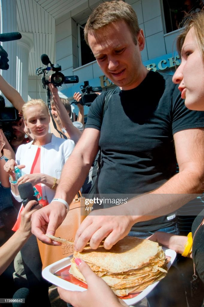 Russia's top opposition leader Alexei Navalny (C), flanked by his wife Yulia, eats a pancake after leaving the courtroom in Kirov on July 19, 2013. A Russian court on Friday unexpectedly freed protest leader Alexei Navalny pending his appeal against a five-year sentence on embezzlement charges, after his jailing prompted thousands to take to the streets in protest. The judge in the northern city of Kirov ruled that keeping President Vladimir Putin's top opponent in custody would deprive him of his right to stand in mayoral elections in Moscow on September 8.