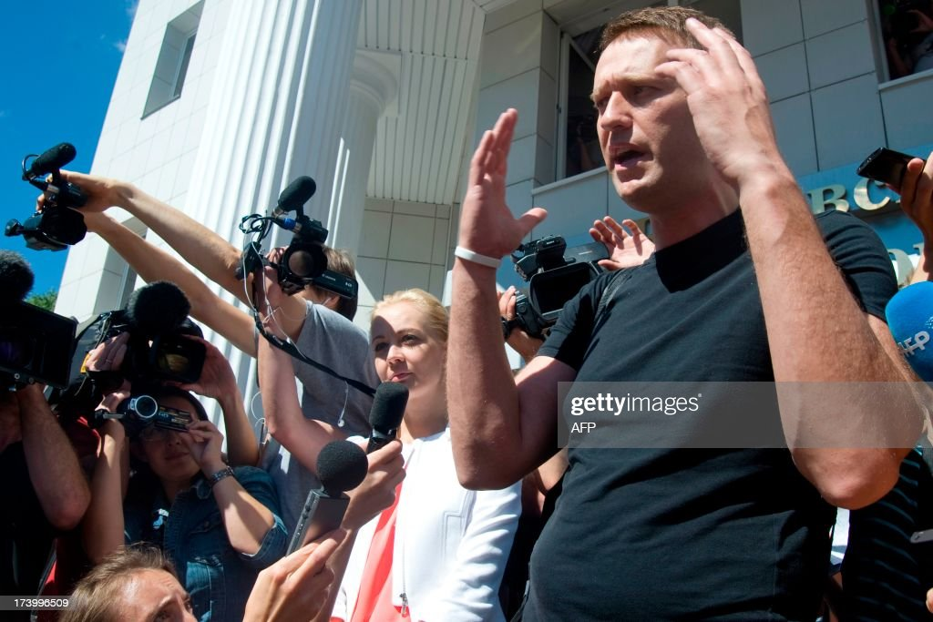 Russia's top opposition leader Alexei Navalny, flanked by his wife Yulia speaks after leaving the courtroom in Kirov on July 19, 2013. A Russian court on Friday unexpectedly freed protest leader Alexei Navalny pending his appeal against a five-year sentence on embezzlement charges, after his jailing prompted thousands to take to the streets in protest. The judge in the northern city of Kirov ruled that keeping President Vladimir Putin's top opponent in custody would deprive him of his right to stand in mayoral elections in Moscow on September 8. AFP PHOTO/SERGEI BROVKO