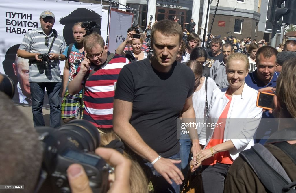 Russia's top opposition leader Alexei Navalny holds the hand of his wife Yulia after leaving the courtroom in Kirov on July 19, 2013. A Russian court on Friday unexpectedly freed protest leader Alexei Navalny pending his appeal against a five-year sentence on embezzlement charges, after his jailing prompted thousands to take to the streets in protest. The judge in the northern city of Kirov ruled that keeping President Vladimir Putin's top opponent in custody would deprive him of his right to stand in mayoral elections in Moscow on September 8.