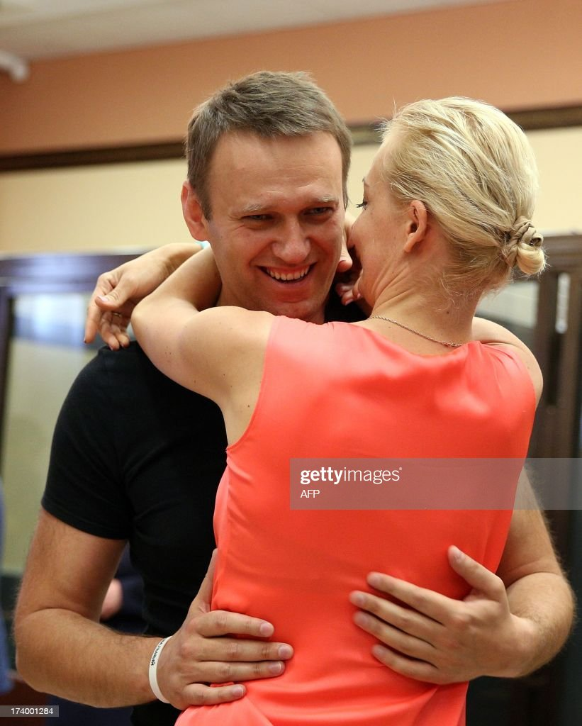 Russia's top opposition leader Alexei Navalny hugs his wife Yulia in the courtroom in Kirov on July 19, 2013. A Russian court on Friday unexpectedly freed protest leader Alexei Navalny pending his appeal against a five-year sentence on embezzlement charges, after his jailing prompted thousands to take to the streets in protest. The judge in the northern city of Kirov ruled that keeping President Vladimir Putin's top opponent in custody would deprive him of his right to stand in mayoral elections in Moscow on September 8.