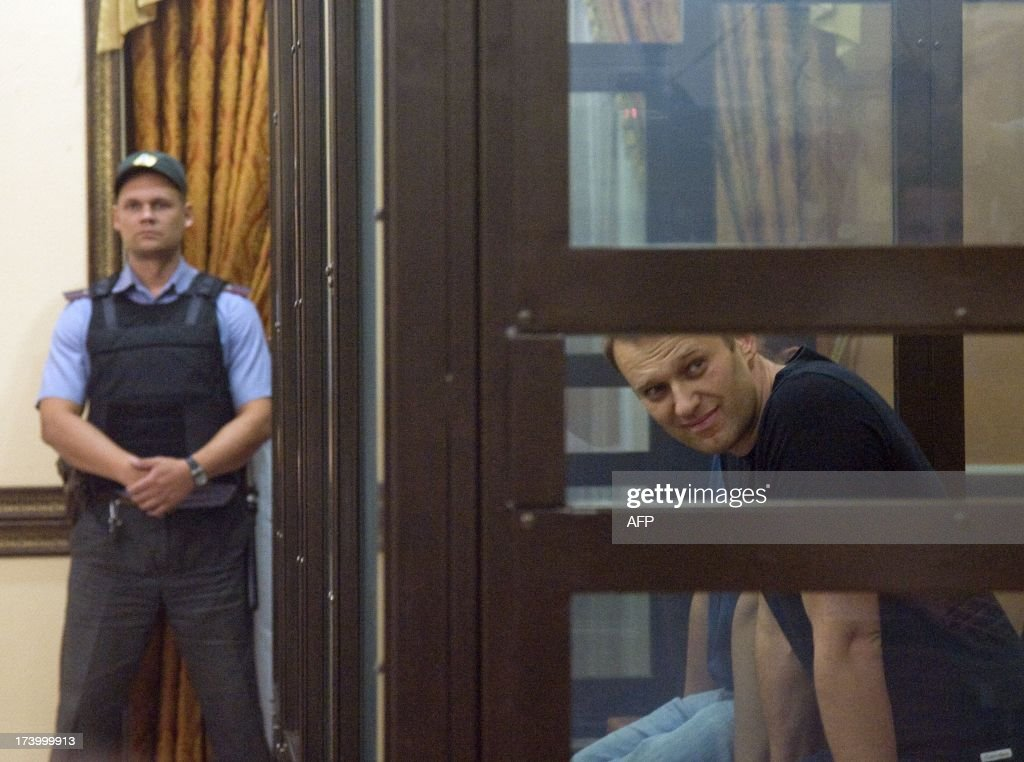 Russia's top opposition leader Alexei Navalny sits in the courtroom in Kirov on July 19, 2013. A Russian court on Friday unexpectedly freed protest leader Alexei Navalny pending his appeal against a five-year sentence on embezzlement charges, after his jailing prompted thousands to take to the streets in protest. The judge in the northern city of Kirov ruled that keeping President Vladimir Putin's top opponent in custody would deprive him of his right to stand in mayoral elections in Moscow on September 8. AFP PHOTO/SERGEI BROVKO