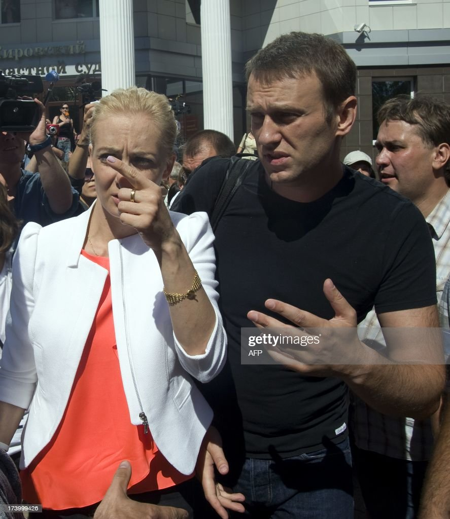 Russia's top opposition leader Alexei Navalny speaks with his wife Yulia after leaving the courtroom in Kirov on July 19, 2013. A Russian court on Friday unexpectedly freed protest leader Alexei Navalny pending his appeal against a five-year sentence on embezzlement charges, after his jailing prompted thousands to take to the streets in protest. The judge in the northern city of Kirov ruled that keeping President Vladimir Putin's top opponent in custody would deprive him of his right to stand in mayoral elections in Moscow on September 8.