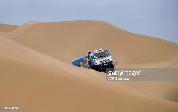 Russia's truck driver Eduard Nikolaev codrivers Evgeny Iakolev and Vladimir Rybakov ride over sand dunes as they compete during the Stage 12 of the...