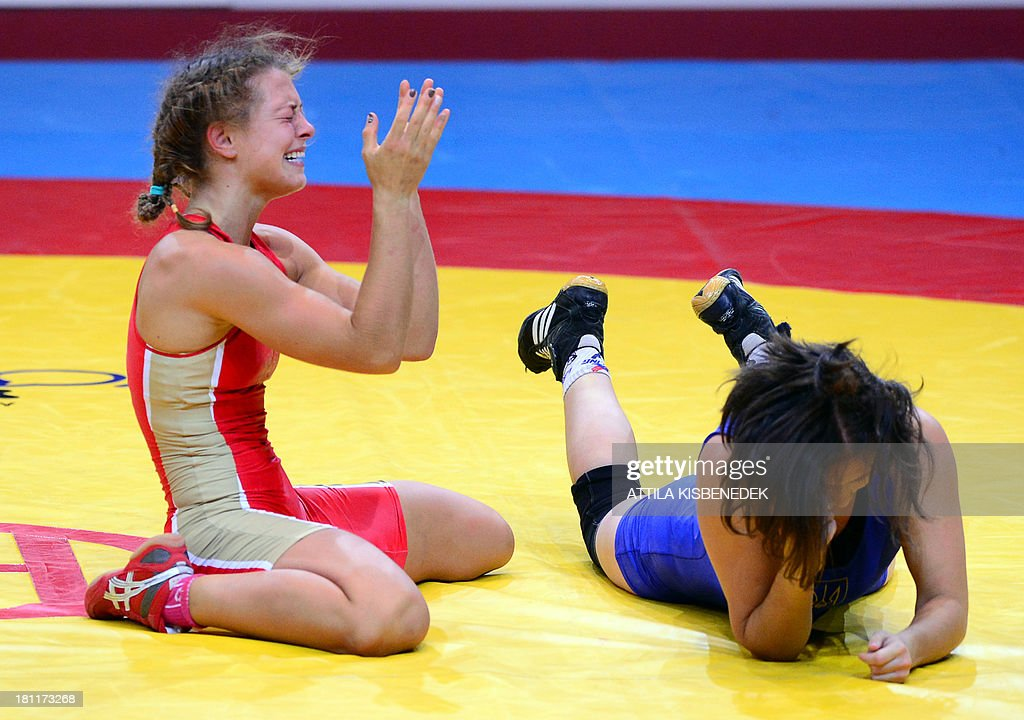 Russia's Valeriia Koblova (red) celebrates her victory over Ukraine's Iryna Husyak (blue) during the women's free style 55 kg category for bronze of the FILA World Wrestling Championships in Budapest on September 19, 2013. Koblova won te bronze medal.