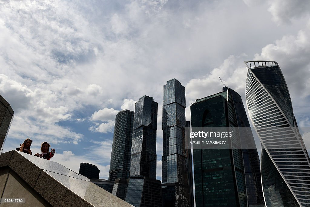 Russia's women are pictured on the bank of Moscow river with the buildings of the Moscow International Business Center (Moskva City) seen in the background in Moscow on May 30, 2016. / AFP / VASILY