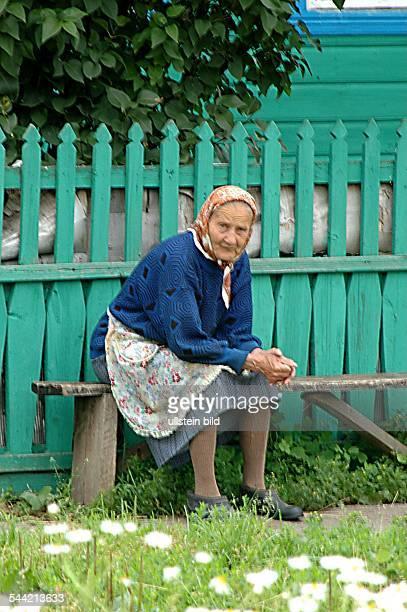 Eine alte Baeuerin ruht sich auf einer Holzbank von der Arbeit aus