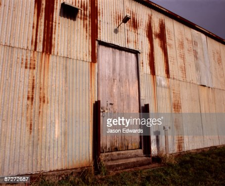 Rust eats away at a corrugated tin shed wall on a farm in Tasmania. : Stock Photo