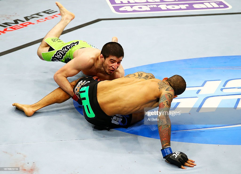Rustam Khabilov of Russia takes down Yancy Medeiros who breaks his fall with his hands injuring himself in their lightweight bout during the UFC 159 event at the Prudential Center on April 27, 2013 in Newark, New Jersey.