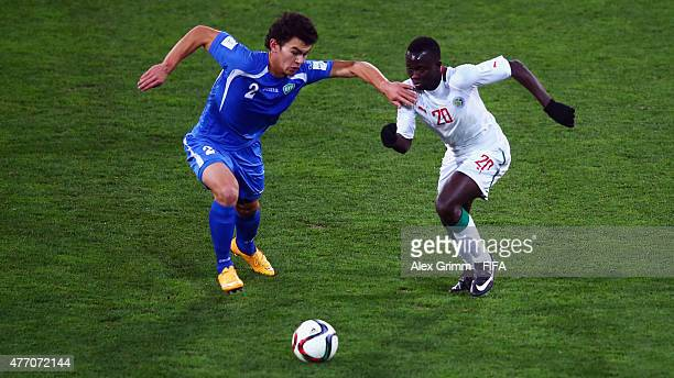 Rustamjon Ashurmatov of Uzbekistan is challenged by Remi Nassalan of Senegal during the FIFA U20 World Cup New Zealand 2015 Quarter Final match...