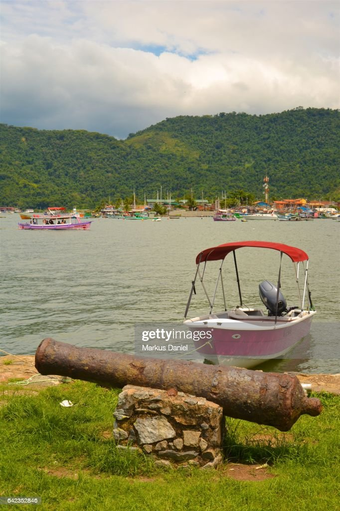Rusted ancient defensive cannon and day trip tourist boats in Paraty, Rio de Janeiro : Stock Photo
