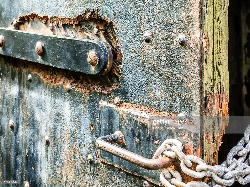 Rusted bolts, latch, chain and handle on door
