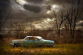 Rusted car in dilapidated urban field