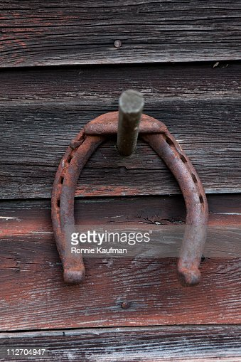 Rusted Horseshoe Hanging On Wooden Wall Stock Photo