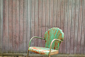 Rusted lawn chair by fence