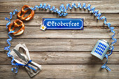 Rustic background for Oktoberfest with Bavarian white and blue streamer, pretzel, bier stein and silverware