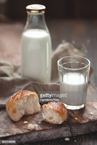 Rustic bottle of milk and bread on a wooden table.