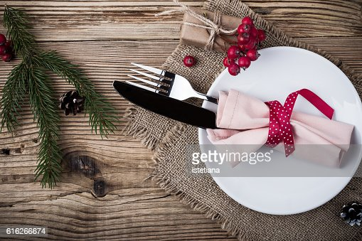 Rustic Christmas place setting,  plate, knife and fork wrapped with napkin on rustic wooden table, top view. Winter holiday theme,  Happy New Year decoration with copy space : Stock Photo