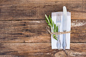 Table place setting with old silverware and wooden table.
