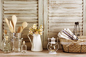 Rustic kitchen still life: wire basket with towels stack, galvanized buckets with wooden spoons, jug with roses bunch, glass bottles and lantern against vintage wooden shutters. Filtered toned image.