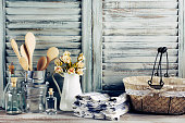 Rustic kitchen still life: wire basket, galvanized buckets with wooden spoons, jug with roses bunch, towels stack and glass bottles against vintage wooden shutters. Filtered toned image.