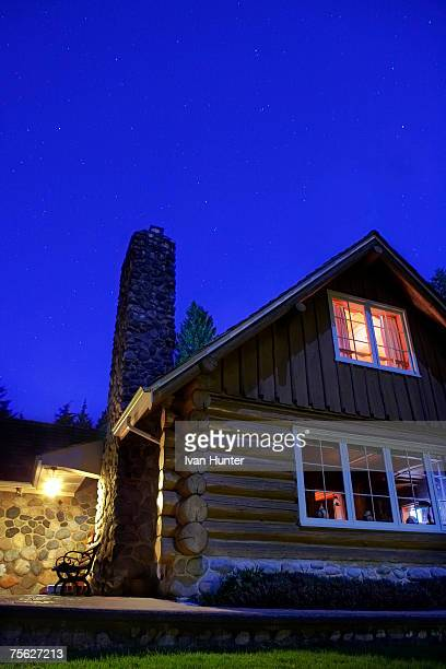 Rustic log cabin at dusk, low angle view