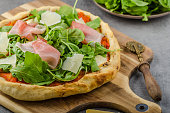 Rustic pizza with arugula, Parma ham and Parmesan