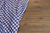 Rustic Picnic Wooden Table With Blue Folded Checkered Tablecloth, Top View, Copy Space