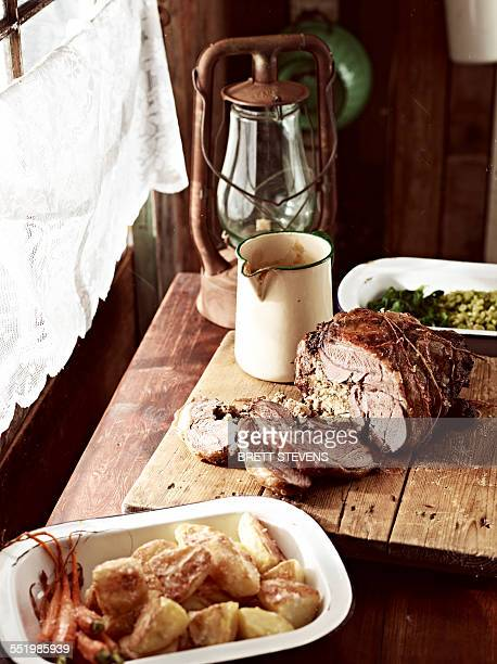 Rustic table with roasted goose on chopping board and roasted vegetables