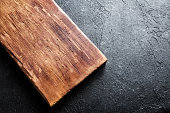 Rustic wooden cutting board on black stone background close up - rustic empty copy space for text, design element
