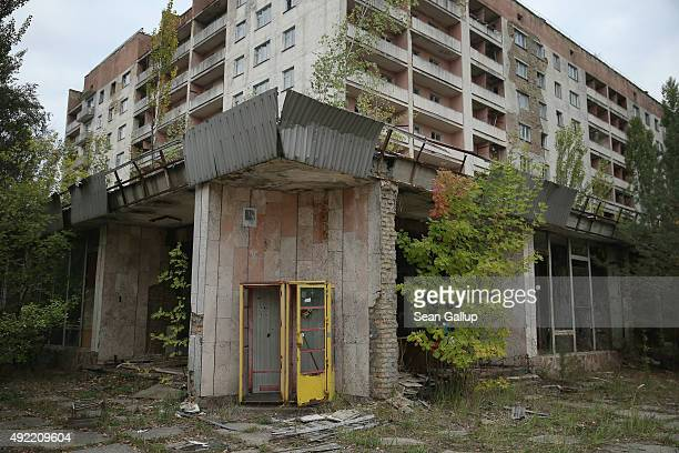 A rusting phone booth stands outside an abandoned furniture store and apartment building on September 29 2015 in Pripyat Ukraine Pripyat lies only a...