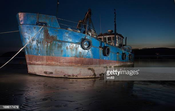Rusting ship on sandbank after sunset