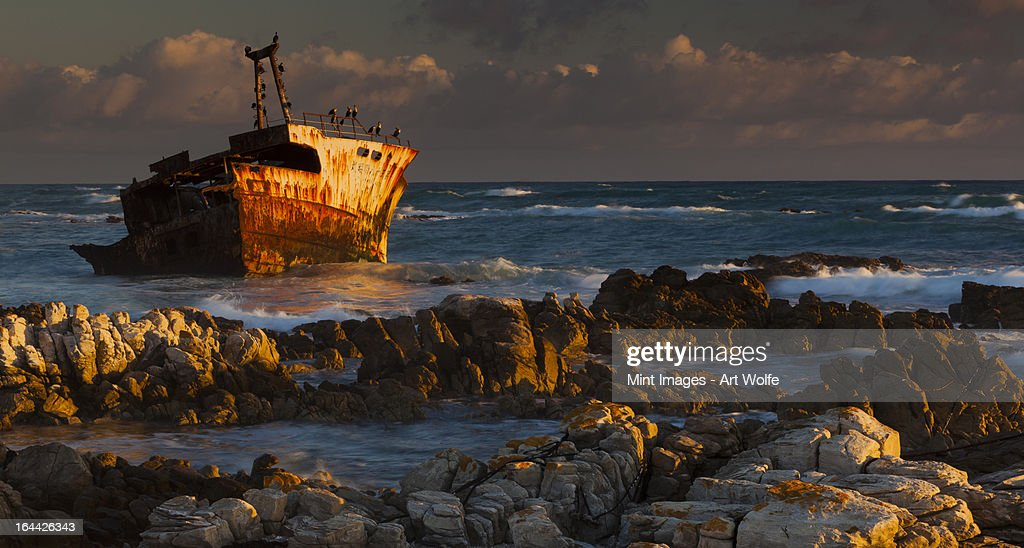 A rusting wreck, an abandoned ship off the shore of Arniston, on the shores of Cape South. : Stock Photo