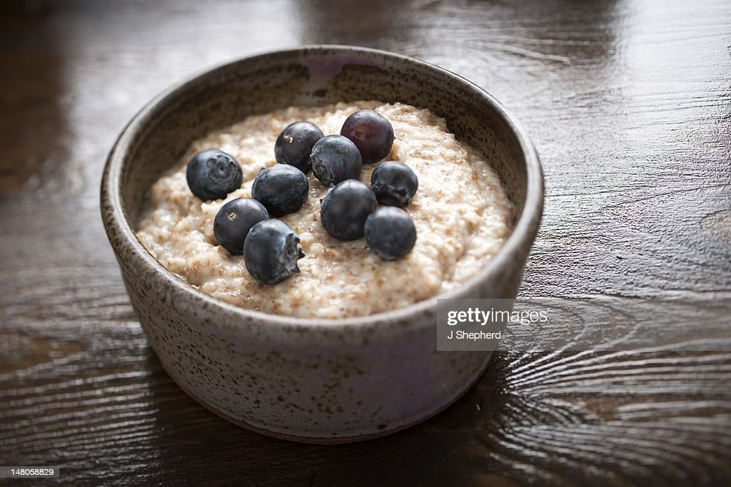 A rustiv bowl of porridge with blueberries : Stock Photo