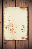 An old blank rusty, weathered and dirty sign on a wooden fence.