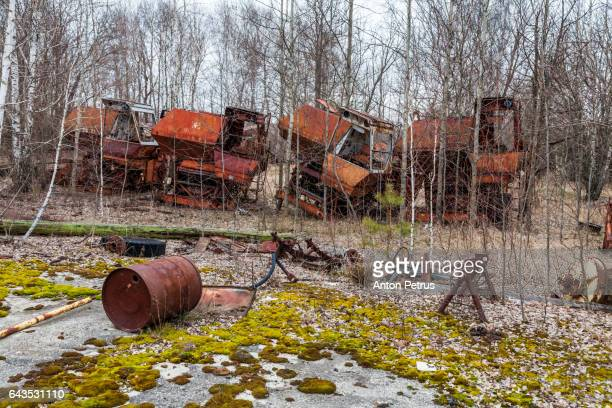 Rusty harvesters in an abandoned farm. Chernobyl zone, Ukraine