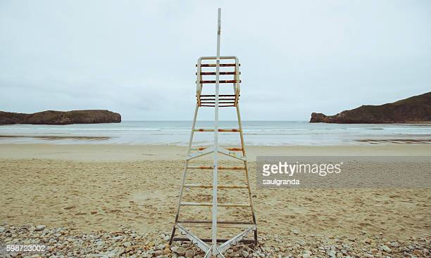 Rusty lifeguard chair in the middle of a beach