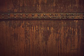 A rusty metal surface texture with rivets.