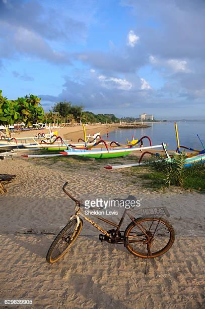 Rusty old bike on Balinese beach at sunrise