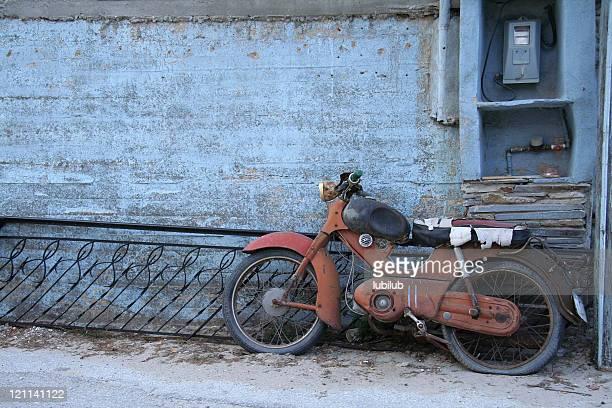 Rusty vieja motocicleta en pared azul en Grecia