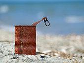 Rusty tin can on the beach with blue sea.