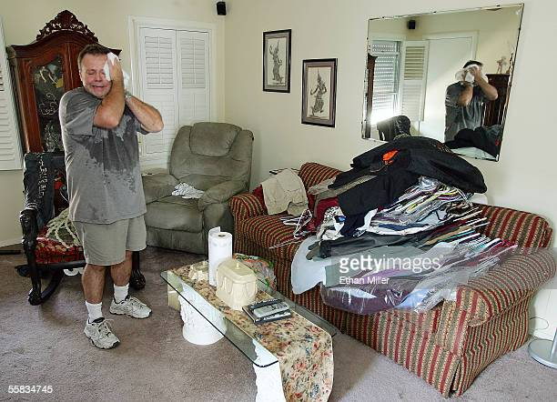 Rusty Toups wipes away sweat as he salvages clothes from the largely unaffected second floor of his home in the Lakeview District October 1 2005 in...