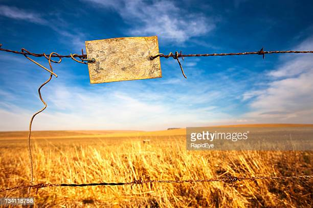 Rusty, unreadable sign on a barbed-wire farm fence