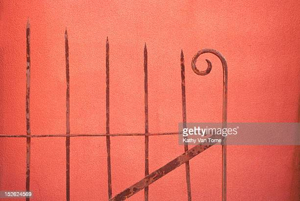 Rusty wrought Iron gate in front of stucco wall