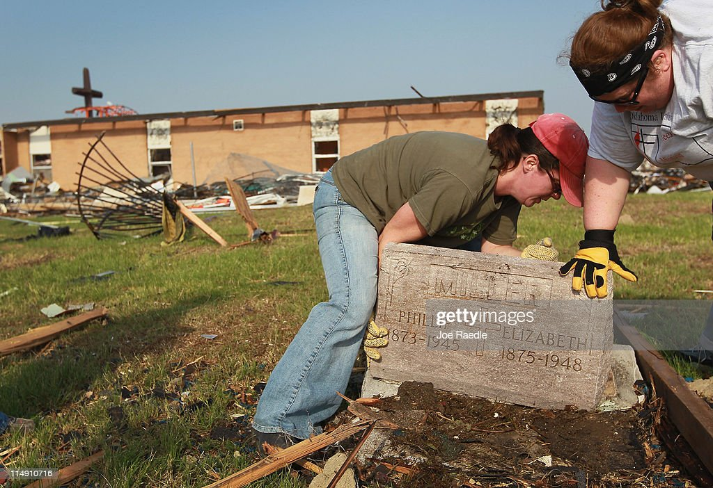 Ruth Ann West (L) and Ashley Rouse right a headstone as they and other work on clearing debris in Mount Calvary cemetery behind St. Mary's church after a massive tornado passed through the town killing at least 132 people on May 28, 2011 in Joplin, Missouri. As the town continues the process of recovering from the storm over 150 people are still missing and funerals have begun for the victims of the deadly tornado that struck on May 22.