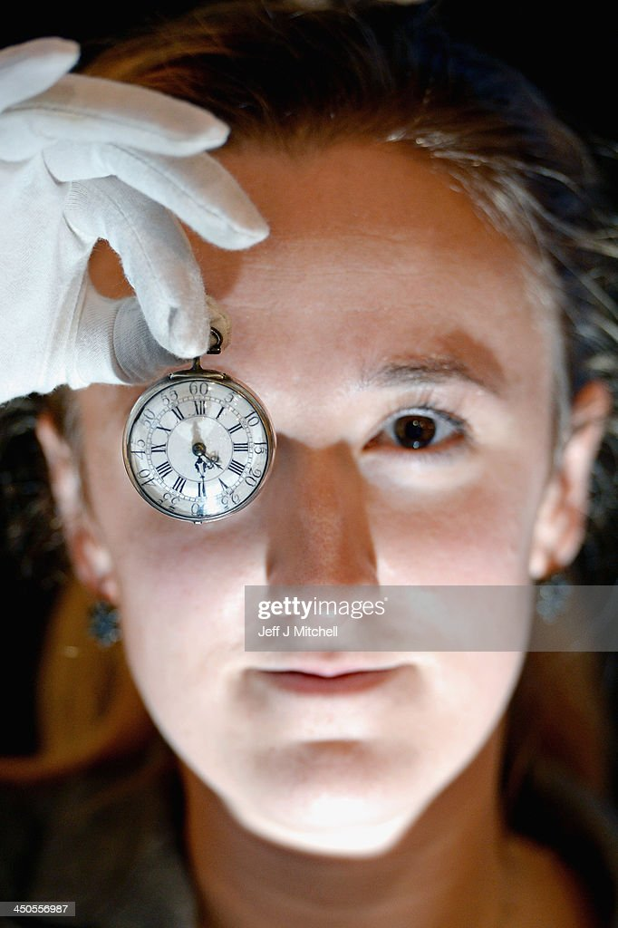 Ruth Davis jewellery specialist at Lyon & Turnbull holds a pocket watch that belonged to Robert Burns on November 19, 2013 in Edinburgh, Scotland. The watch that belonged to Robert Burns valued at £2,500 will be sold at Lyon & Turnbull on the November 27th.The silver pair cased pocket watch contains a paper insert with bird and heart motifs and initials in ink from his wife Jean Armour, the rear cover was engraved with RobT Burns Mauchline 1786.