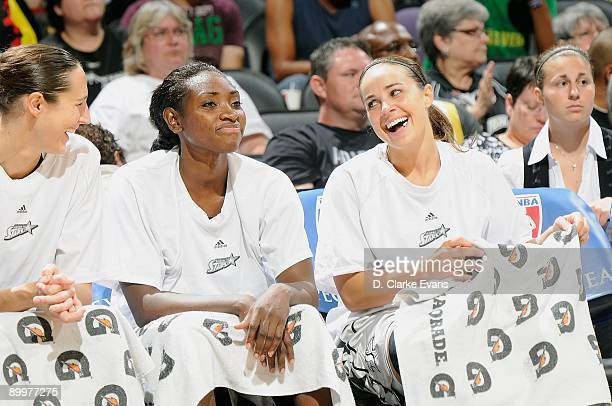 Ruth Riley Sophia Young and Becky Hammon of the San Antonio Silver Stars rest on the sidelines during the WNBA game against the Phoenix Mercury on...