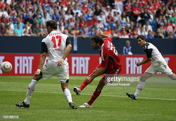 Ruud van Nistelrooy of Hamburg scores the first goal against Kevin Pezzoni of Koeln and Mato Jajala of Koeln during the LIGA total Cup 2010 third...